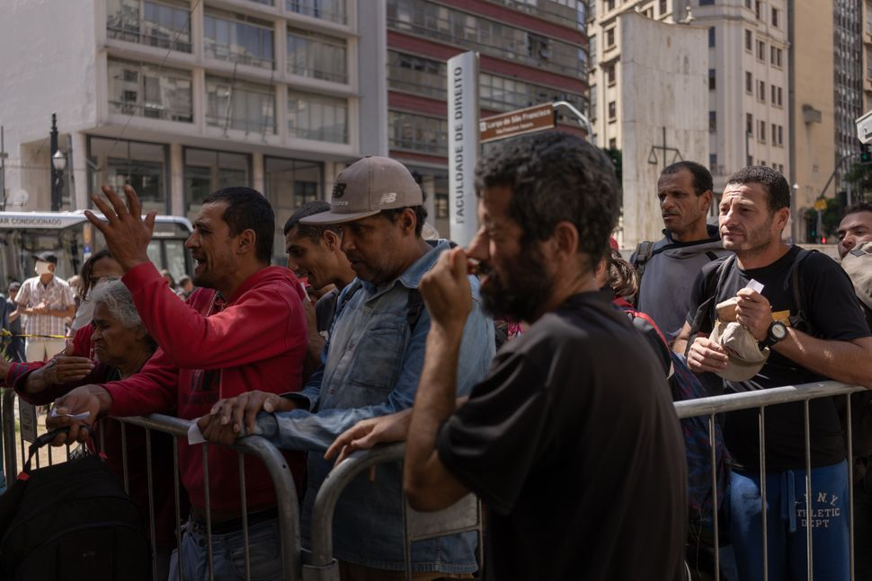 Homeless people queue for food at a medical screening center in São Paulo.