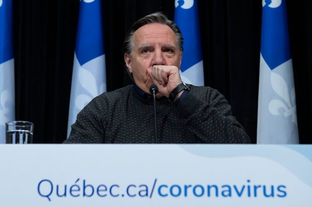 Quebec Premier Francois Legault coughs into his hand as he speaks at a news conference on the COVID-19...