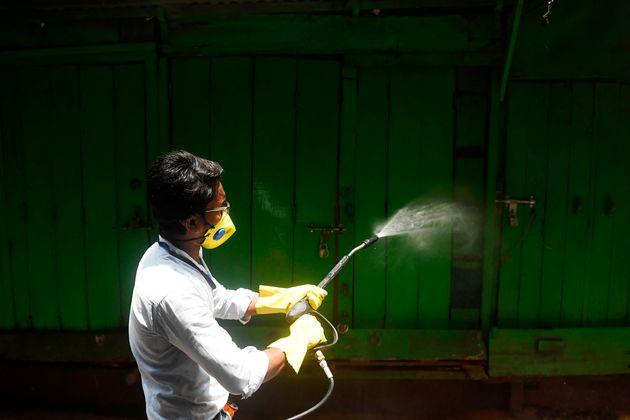 A municipal worker sprays disinfectant as a preventive measure against the COVID-19 coronavirus in Kolkata...