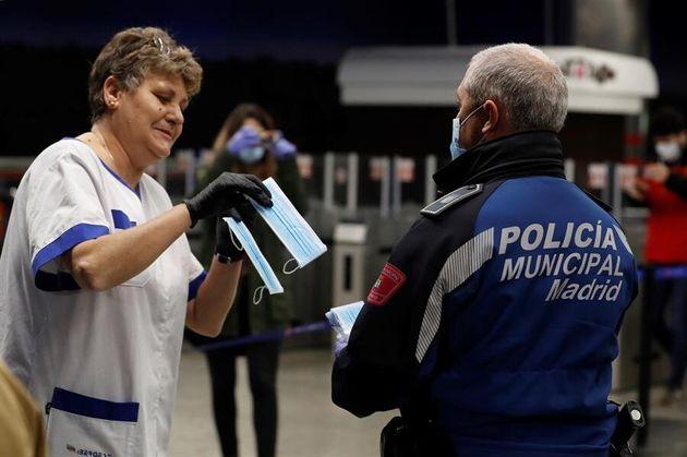 Policías entregan una mascarilla a una mujer en la estación de metro de Nuevos Ministerios en Madrid,...