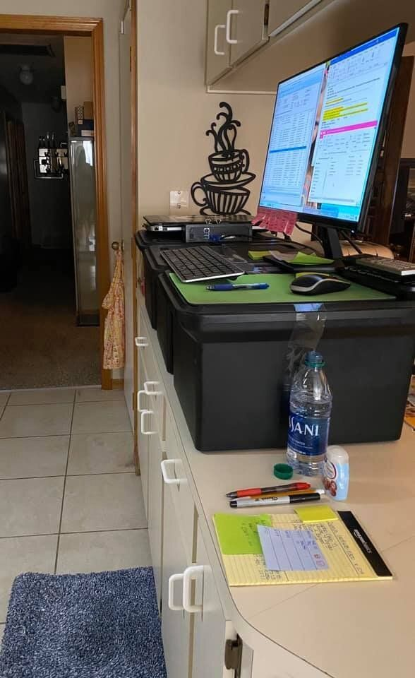 Billing analyst Elizabeth Goecke created a standing desk with three plastic storage boxes on her kitchen counter, and made a padded mat using two bath rugs folded in half.
