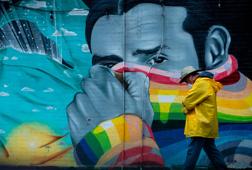 A man wearing a mask passes a mural on April 13, 2020 in New York City.