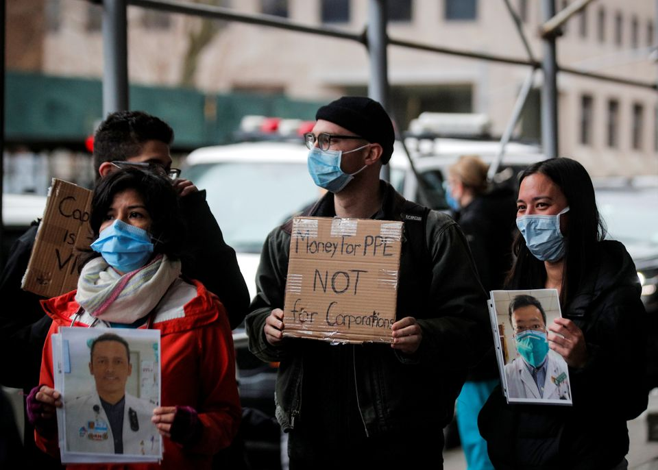 Health care workers at Mount Sinai Hospital hold photos of sick colleagues during a protest demanding...