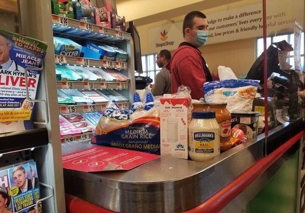 ニューヨーク・クイーンズにあるスーパーマーケット。マスクをした店員が保護シールドの向こうでレジを打つ