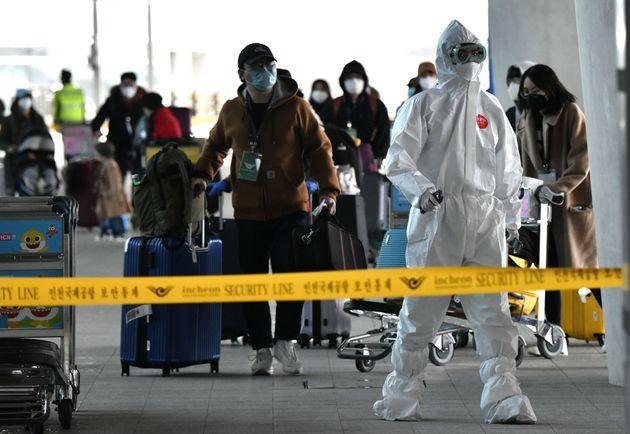 (자료사진) 보호복을 착용한 한 경찰관이 인천국제공항으로 도착한 승객들을 안내하고 있다. 2020년