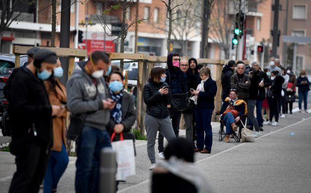 Dans l'attente d'un dépistage du Covid-19, des personnes font la queue devant l'Institut Hospitalo-Universitaire...