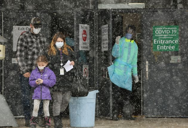 An Ottawa Public Health officer, right, waves to the next person in line at a COVID-19 testing centre...