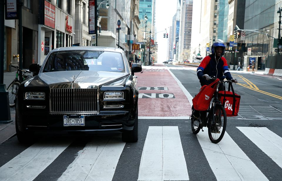 A delivery worker rides past a Rolls Royce amid the coronavirus pandemic on April 5, 2020 in New York
