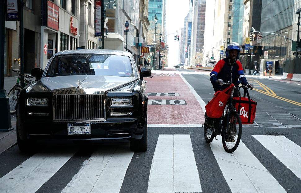 A delivery worker rides past a Rolls Royce amid the coronavirus pandemic on April 5, 2020 in New York City.