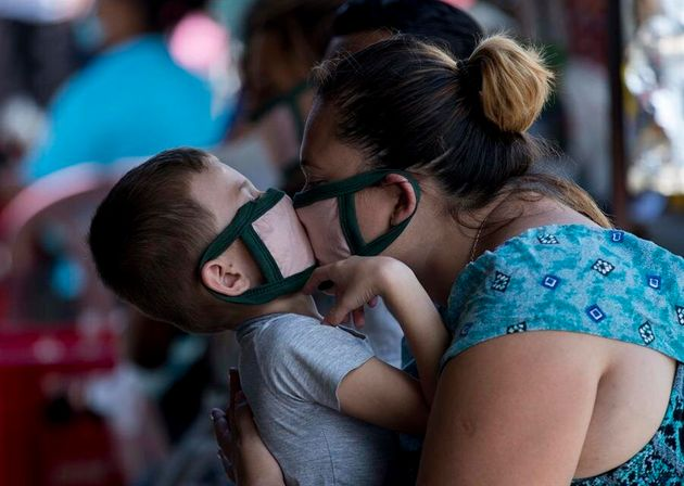 Una mujer besa a su hijo con
