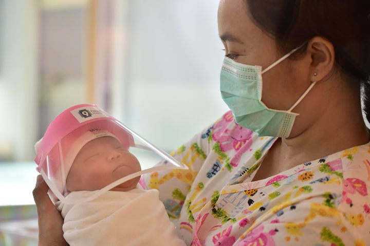 A nurse at Praram 9 Hospital in Bangkok, Thailand, holds a newborn baby wearing a face shield, in an effort to halt the spread of the COVID-19 coronavirus.