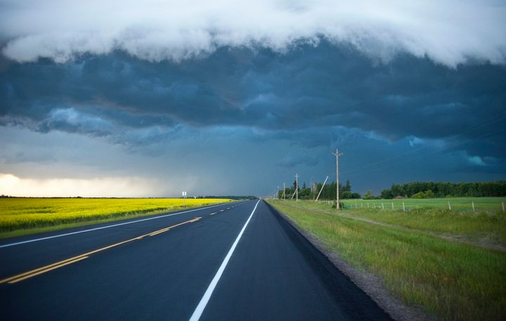 This undated stock photo shows an empty two-lane highway in rural Alberta, with the dark clouds of a storm on the horizon.