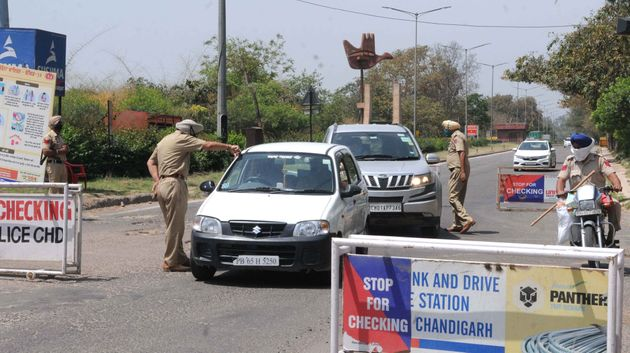 Police personnel screen vehicles for identity cards during the lockdown, at Chandigarh - Zirapur boarder...