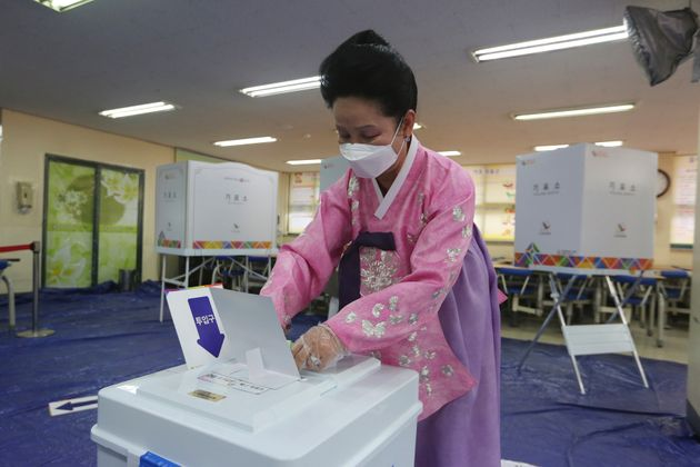 A woman wearing a face mask to help protect against the spread of the new coronavirus casts a vote for...