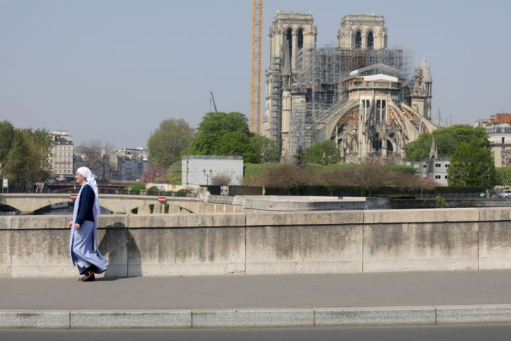 """A nun is seen walking on the """"De La Tournelle bridge"""" with Notre Dame Cathedral in the background on April 10, 2020, in Paris"""