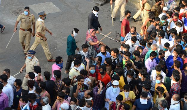 Police try to control migrant workers protesting against the the extension of the lockdown in Mumbai,...