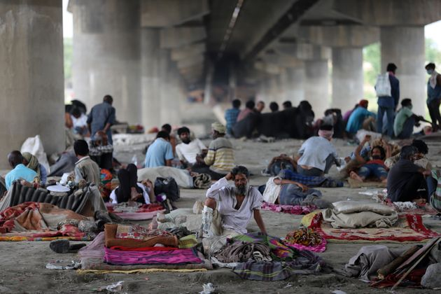 Migrant workers and homeless people take refuge under a bridge on the banks of the Yamuna River in New...