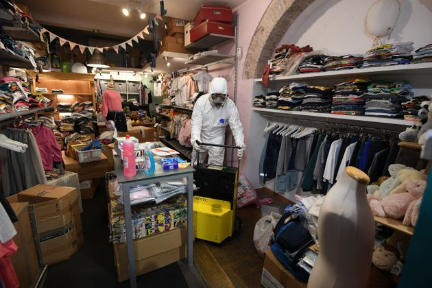 A worker in protective gear inspects a children's store in Rome's Trastevere district as the Italian...