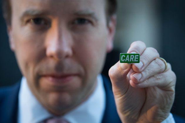 Health secretary Matt Hancock showing the new 'Care' badge, described as a