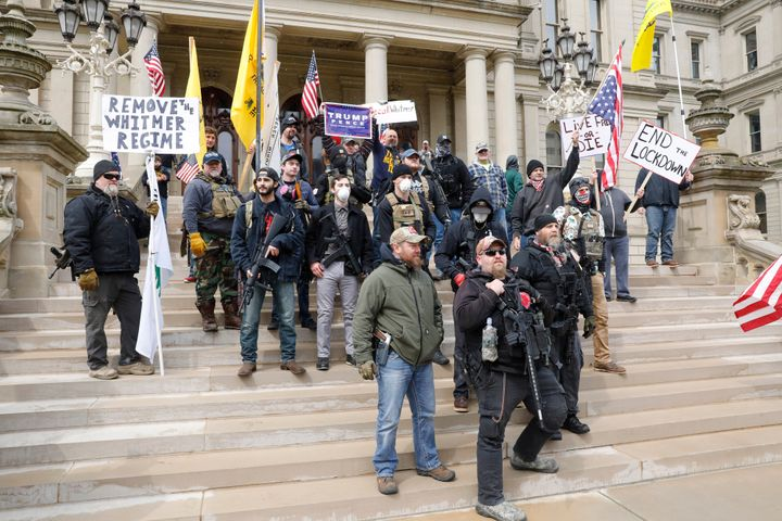 """People take part in a protest for """"Michiganders Against Excessive Quarantine"""" at the Michigan State Capitol in Lansing, Michi"""
