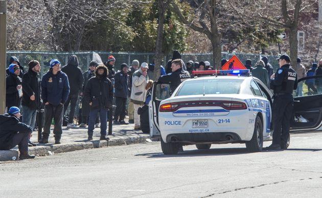La police rappelle aux gens l'importance de maintenir la distanciation sociale alors qu'ils font la queue...