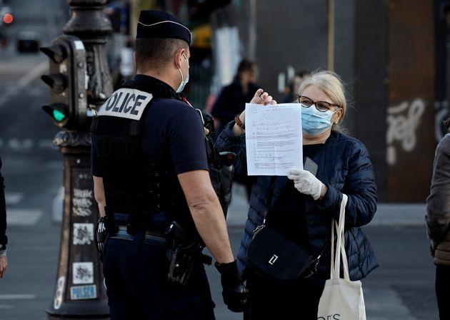 Durant la période de confinement due au coronavirus, un policier vérifie l'attestation...
