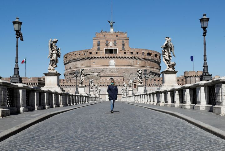 A woman wearing a protective mask walks outside Castel Sant'Angelo in Rome, Italy, on March 23.