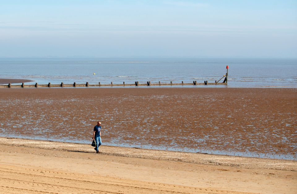 A man walks along the beach in Cleethorpes as the UK continues in lockdown to help curb the spread of...