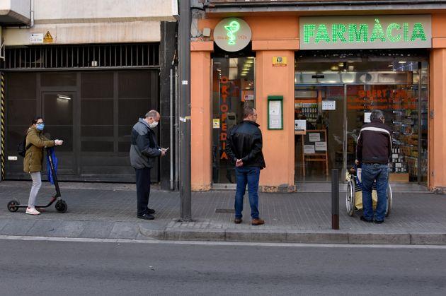 Varios ciudadanos hacen cola para la farmacia en Hospitalet