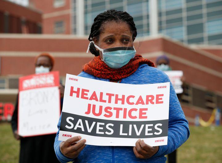Rehabilitation nurse Edith Ihejirika holds a sign as she participates in a demonstration outside the emergency entrance to Ja