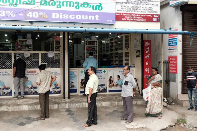 People queue in a line at a pharmacy in Kochi on March 25,
