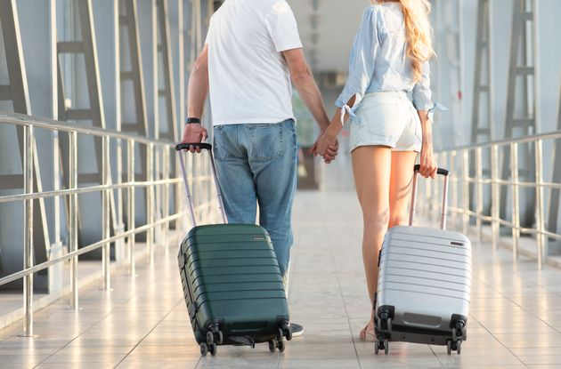 Young couple carrying luggage in airport terminal, holding hands and looking at