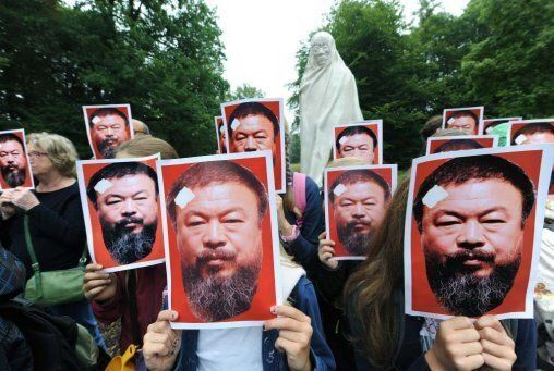 """<em>Supporters of  Ai in Kassel, Germany, pose with portraits of the dissident artist as part of the project """"All for Ai Wei"""