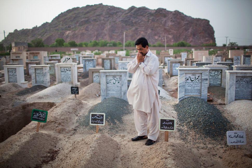 <em>Muhammad Munawar prays at the grave of his slain son, 17-year-old Waleed, in Chenab Nagar, Pakistan. Waleed, a medical st