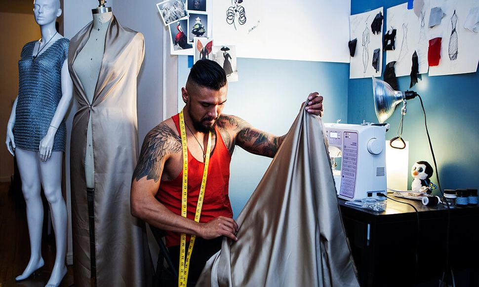 <em>Banks at work at his sewing machine. He told HuffPost that he hopes to launch a capsule menswear collection at the end
