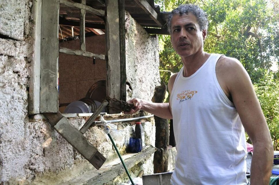 <em>José Claudio Pinto holds the lock that was once used to keep the windows of quilombo Sacopã's kitchen shut.  (Carolina Ra