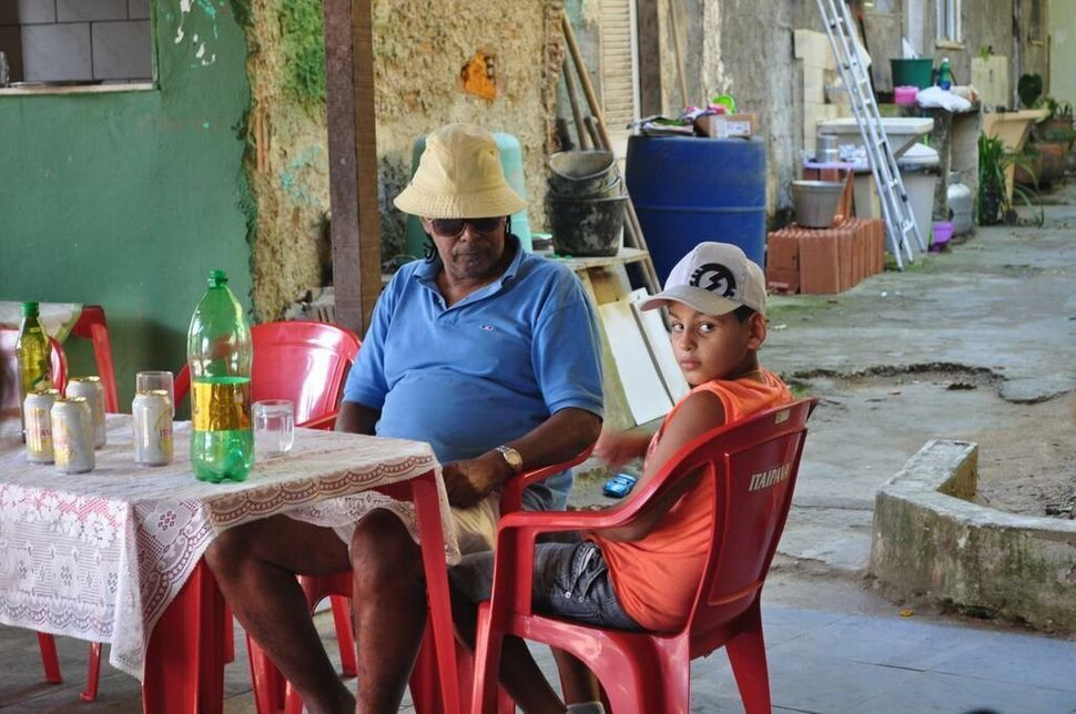 <em>Luiz Pinto and his grandson in the area of their quilombo that once hosted lively parties. Neighbors' complaints have sin