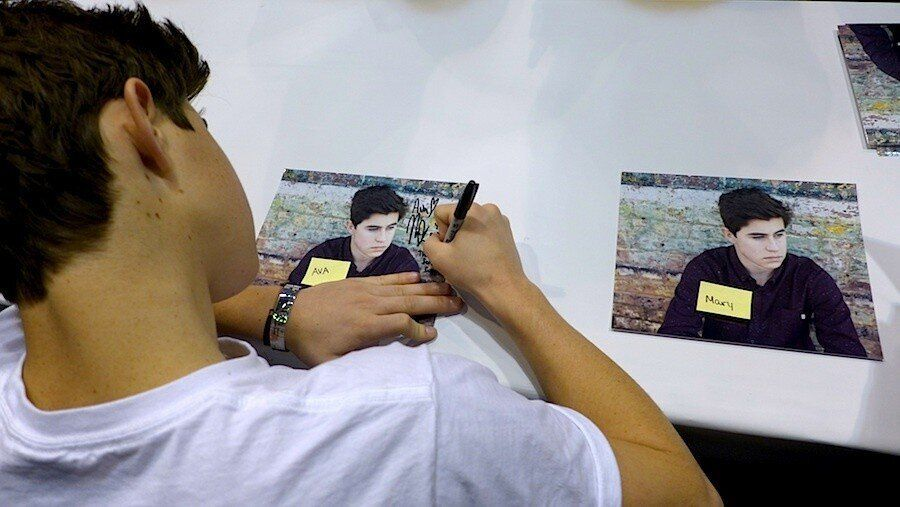 <em> Nash signs two of several hundred photos he autographed in the course of one afternoon at Wizard World. (Photo by Bianca