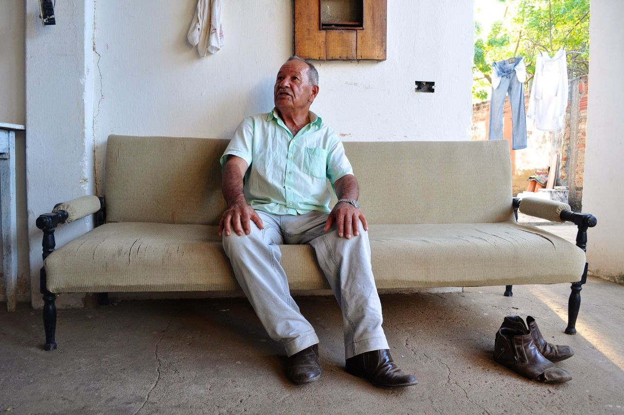 """<div class=""""feature-caption""""><em>Hélio Pereira Pinto, seated on a sofa at his home in Barra do Parateca, is one of several people with whom the quilombo association has a land dispute. (Carolina Ramirez/The Huffington Post)</em></div>"""