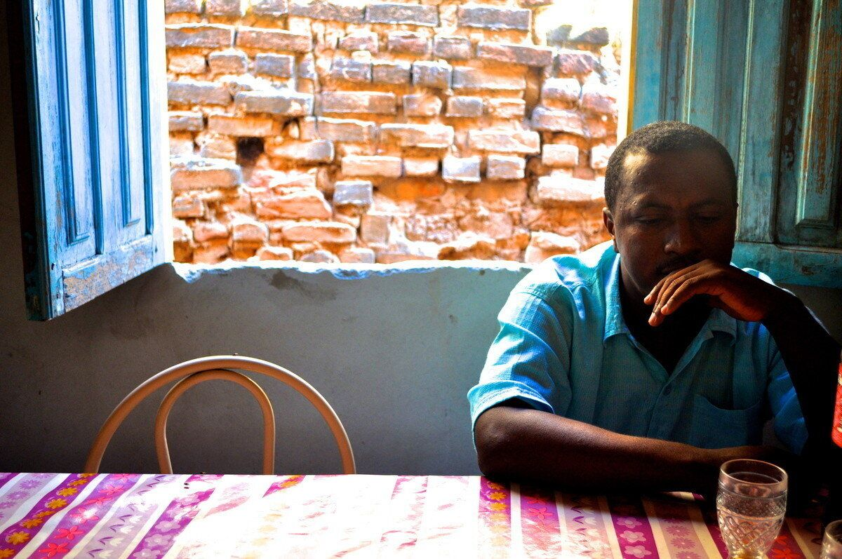 """<div class=""""feature-caption""""><em>Almir Viera Pereira seated in his mother's kitchen in the town of Barra do Parateca, Brazil. (Carolina Ramirez/The Huffington Post)</em></div>"""