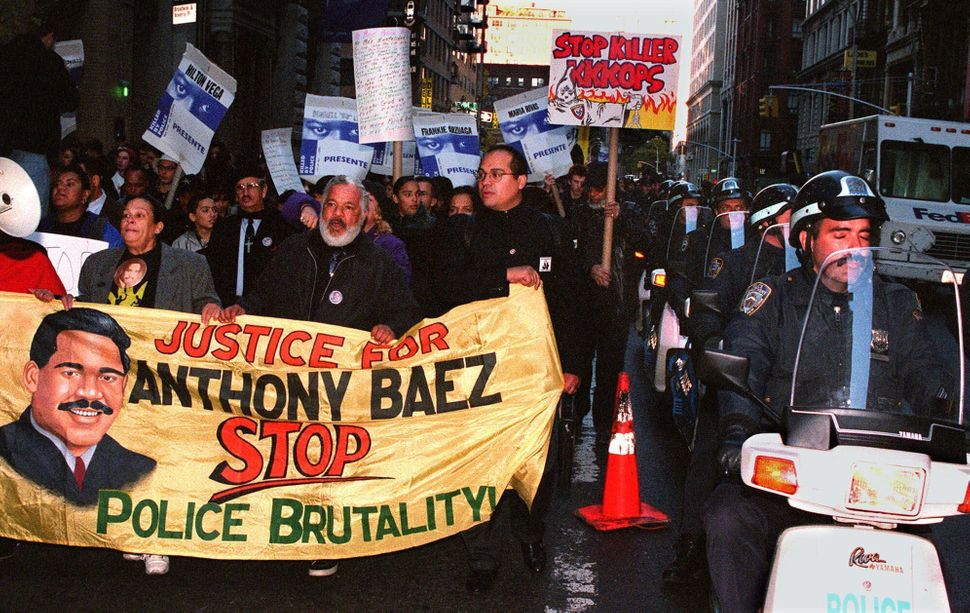 <em>Iris, left, and Ramon Baez, second from left, the parents of Anthony Baez, carry a banner as they march with at least 3