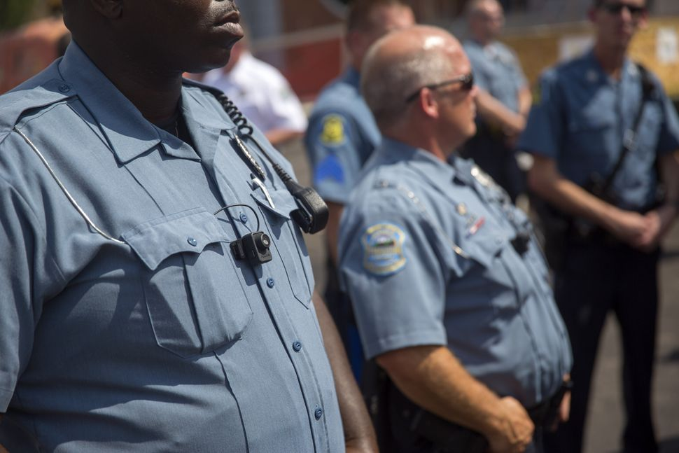 <em>Members of the Ferguson Police Department wear body cameras during a rally on Aug. 30, 2014, in Ferguson, Missouri. Pol