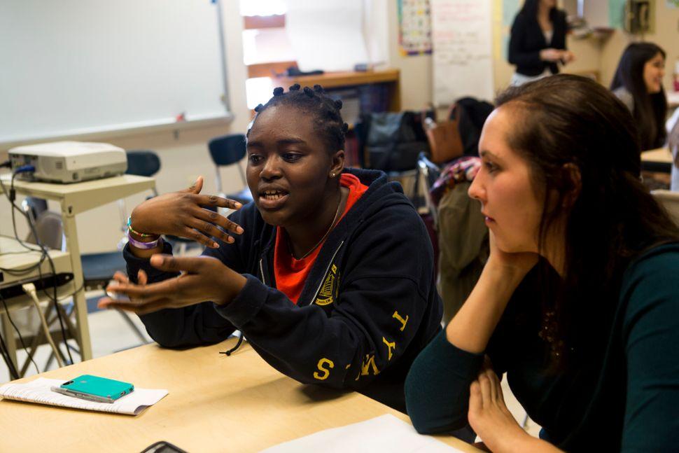 <em>Amanda de la Torre, 26, listens as her mentee Angela Opoku, 15, speaks to the group. </em>