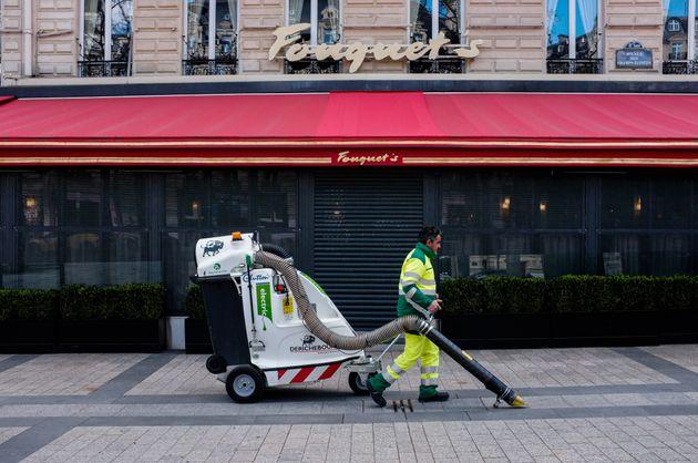 Un employé chargé de la propreté nettoie la rue devant le Fouquet's sur les Champs-Elysées...