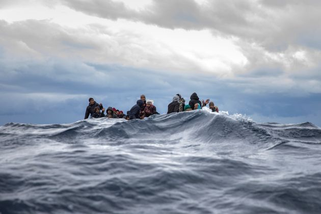 Men from Morocco and Bangladesh react on an overcrowded wooden boat, as aid workers of the Spanish NGO...