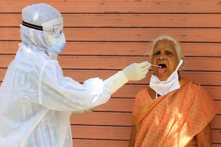 A medic collects a swab sample of an elderly woman during a door-to-door examination of COVID-19 during a curfew imposed in Jaipur, Rajasthan on April 15.