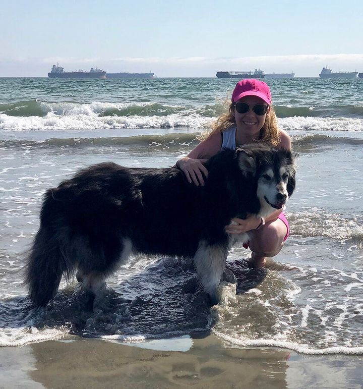 Black with her dog, Bear, at Pink Beach.