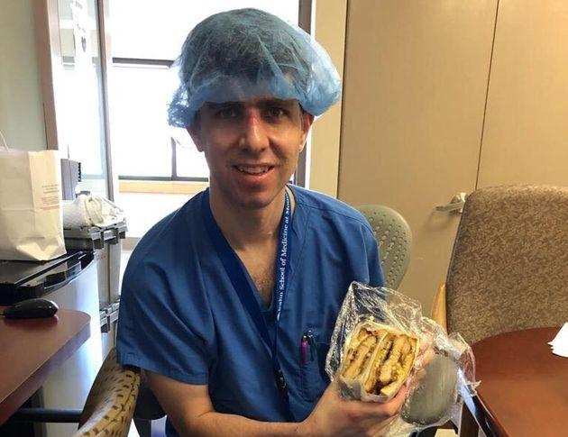 差し入れのサンドイッチを食べる医師