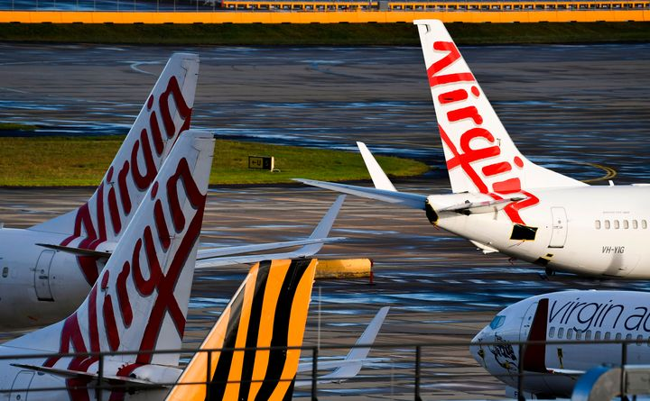 Planes from Australian airlines Tiger Air and Virgin sit idle on the tarmac at Melbourne's Tullamarine Airport on April 12, 2020.