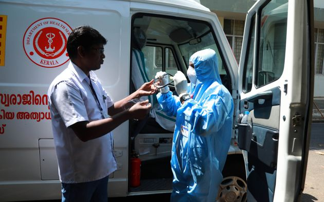 An ambulance driver (R) of Ernakulam medical college puts on gears up with protective apparel as he prepares...